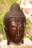 Buddha-Statue mit einem Blumenhintergrund Stockfotos