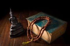 Buddha-Statue mit Halskette und Antikenbuch Lizenzfreies Stockfoto