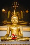 Buddha-Statue mit thailändischer Kunstarchitektur und großer Buddha-Goldhintergrund in der Kirche Lizenzfreies Stockfoto