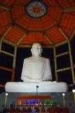 Buddha statue with monks sitting and praying, Anuradhapura, Sri Lanka. Night view of the Buddha statue with monks sitting and praying. Sri Sarananda Maha Royalty Free Stock Images