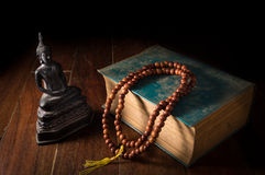 Buddha statue with necklace and antique book. Royalty Free Stock Photo