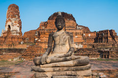 The Buddha statue with old dilapidated temple in background Stock Photos