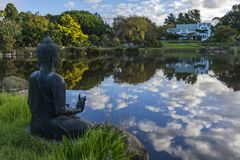 Buddha statue over looking a lake Stock Photos