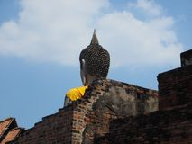 Buddha statue rises above an ancient temple`s walls Royalty Free Stock Photo