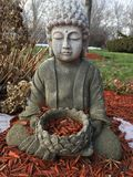 Buddha Meditating. A Buddha statue sits in meditation outdoors in a garden surrounded by woodchips and spots of ice, with a bounty of woodchips in a vessel he is Stock Images
