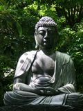 A Buddha statue sitting amongst trees and shrubs. A sitting buddha statue rests against a backdrop of green trees and bushes. The statue is grey stone, and Stock Photos