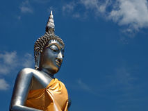 Buddha statue soars into blue sky Royalty Free Stock Photography