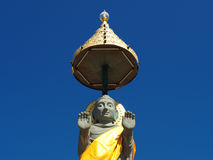 Buddha statue soars into blue sky Stock Photo