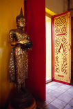 Buddha statue standing next to the doors in a temple. Stock Photo