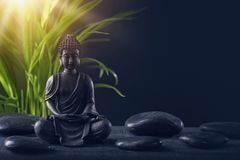 Buddha statue and stones. On a black background stock photos