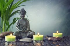 Buddha statue and stones. Buddha statue on a grey background stock images