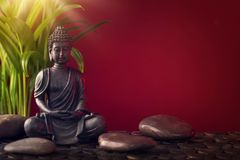 Buddha statue and stones. On a red background royalty free stock photo