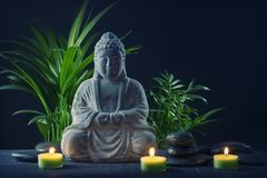 Buddha statue, stones and candles. On a black background stock photo