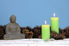 Buddha statue, tinsels and candles. Buddha statue with tinsels, pinecones and two green candles on a wood table against a blue background royalty free stock photos