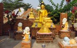 Buddha-Statue und lachende kleine Mönche nähern sich buddhistischem Tempel Lizenzfreie Stockfotos