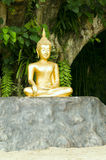 Buddha statue under green tree. Golden Buddha statue under green tree in meditative posture Royalty Free Stock Photo