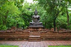 Buddha-Statue unter alter Backsteinmauer Stockfotografie