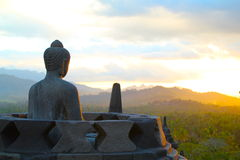 Buddha Statue Watching the Sunset Over Borobodur Temple Royalty Free Stock Image