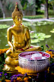 Buddha statue with water bowl. A sitting Buddha statue with water bowl in front to be used for washing the Buddha during the Thai New Year Songkran festival Stock Photo