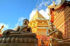 Buddha-Statuen und goldene Pagode gegen klaren blauen Himmel Lizenzfreie Stockfotos