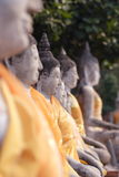Buddha Statues. A line of buddha statues, all dressed in yellow clothes. The focus is only on one of the statues Royalty Free Stock Photos