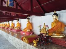 Buddha statues. Aligned Buddha statue with gold bands at Wat Mahathat, NakhornSriThammarat, Thailand Royalty Free Stock Photography