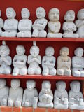 Buddha statues in display. Little Buddha statues in display on shelves Royalty Free Stock Photos