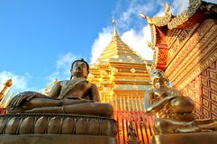 Buddha statues and golden pagoda against clear blue sky Royalty Free Stock Photos