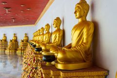 Buddha statues. Golden Buddha statues sit in a row. In one of the Thailand temples Royalty Free Stock Photo