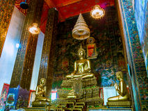 Buddha statues with mural painting around. Royalty Free Stock Images