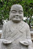 Smiling Buddha statue of natural stone, China royalty free stock images
