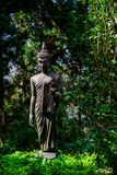 Buddha statues stand among the trees in the background. Royalty Free Stock Photo