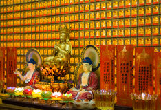 Buddha statuette and beautiful gold decoration in a temple. Buddha sitting on the lotus flower and small lotuses are ahead Stock Photos