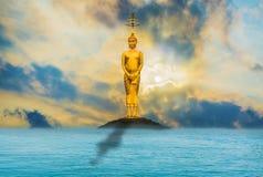 Buddha steht majestätisch ruhig gibt es einen Abendhimmel mit dem Meer als der Hintergrund Stockfoto