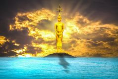 Buddha steht majestätisch ruhig gibt es einen Abendhimmel mit dem Meer als der Hintergrund Stockfotografie