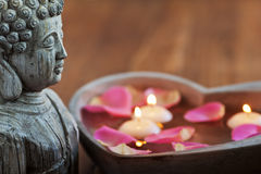 Buddha still life. Buddha figure with a stone heart filled with water floating candles and rose petals Stock Photos