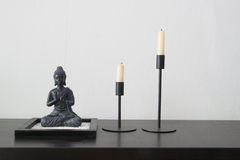 Buddha still life. Buddha sculpture and candles before crepe wallpaper Royalty Free Stock Photo