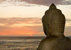 Buddha and sunset. Side view of Buddha overlooking the setting sun stock photo