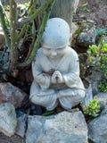 Buddha unter Rosenbusch lizenzfreie stockfotos