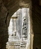 The Buddha on the wall. Buddhist monuments indemnityshi ping hole and small stone statue of Buddha. Ankor Wat is part of a vast network of around a hundred royalty free stock photo