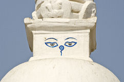 Buddha wisdom eyes on small white stupa in Kathmandu Stock Image