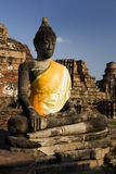 Buddha in yellow, Thailand. Ancient sculpture of a buddha in yellow robes. Temples and pagodas in Ayutthaia, ancient capital of Thai kingdoms, near Bagkok Stock Photography