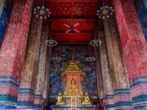 Buddhalagen sitter i biskopsstolen med stora kolonner i linjer Royaltyfri Fotografi
