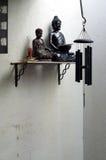 2 buddhas на полке с ладаном и перезвоном ветра Стоковые Изображения RF