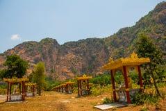 坐Buddhas的许多雕象,在与山的美好的风景中在晴天 Hpa-An,缅甸 缅甸 库存图片