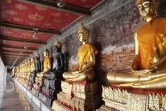 Buddhas que se sienta a piernas cruzadas en una línea Imagen de archivo