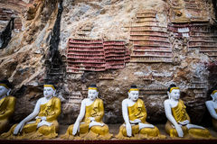Buddhas statues and religious carving in Kaw Goon cave. Hpa-An, Stock Photography