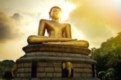 Buddhastaty över scenisk solnedgång Arkivfoto
