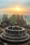 Buddhastaty i öppen stupa i Borobudur när soluppgång arkivfoto