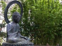 Buddhastaty i en bambudunge Arkivbilder